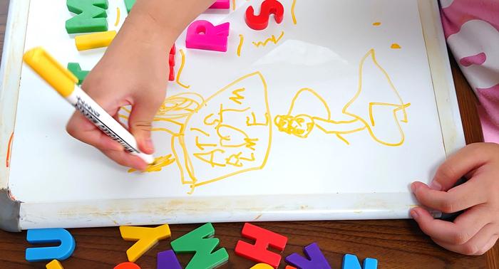 アルファベットを組み合わせて絵を描く女の子