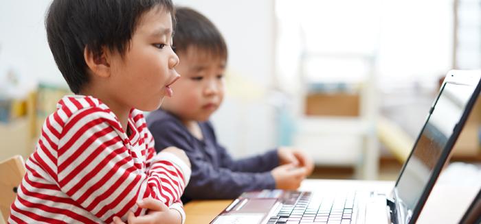 パソコン越しに英会話を教わる男の子たち